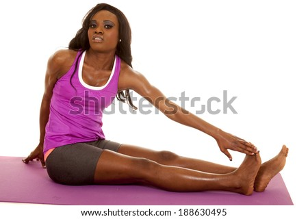 An African American woman sitting on her fitness mat reaching for her toes.