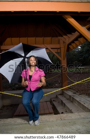 An African American woman under an umbrella - stock photo