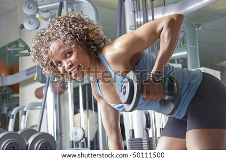 An African American woman working out in the gym with weights - stock photo