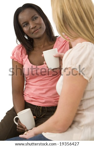 An African American young woman chatting with her friend over a cup of coffee or tea