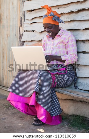 An african lady is learning the ways of a computer.