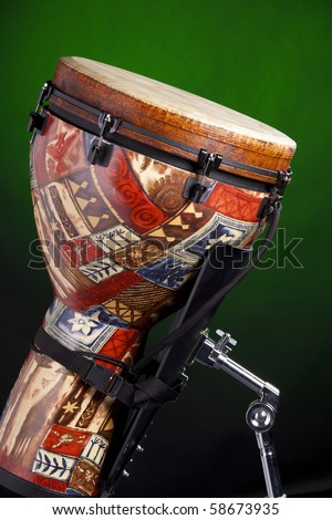 An African Latin djembe or conga drum isolated against a spotlight green background.