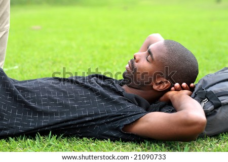 An african man is lying on the green grass and sleeping with his hands behind his head - stock photo