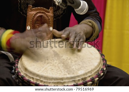 An african man playing a traditional drum by hand - stock photo