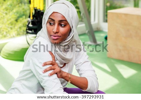 An African Muslim woman is getting rest after a workout in a gym in Dubai, UAE. - stock photo