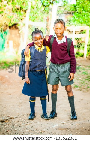 an african older brother proudly standing with his younger sister in their school uniform just before school starts - stock photo