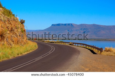 An African road around a table mountain close to a big lake - stock photo