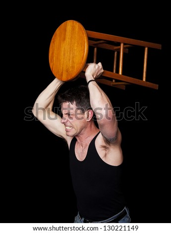 An aggressive, angry man ready to fight with a bar stool in his hands. - stock photo