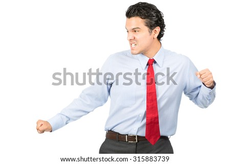An aggressive hispanic male business professional in formal dress shirt, red tie, fierce facial expression strikes a martial arts kung fu pose looking away to side fighting opponent. Half