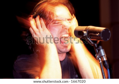 An aggressive music singer recording in a studio.  Lots of mood and atmosphere created with timed exposure with hand-held flash. (some film grain because of the 1600 ISO film used) - stock photo