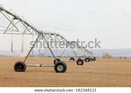 An agricultural center pivot used to irrigate an alfalfa field. - stock photo