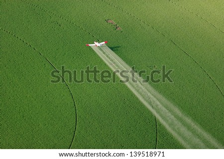 An agricultural crop duster flying low, and spraying a potato field - stock photo