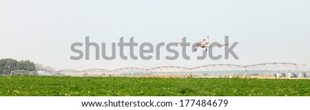 An agricultural crop duster flying low over a potato field, spraying chemicals. - stock photo
