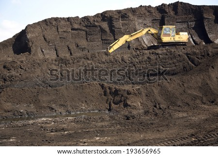 An agricultural digger on a mound of peat which has been extracted from the Somerset Levels in the UK