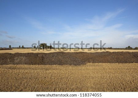 an agricultural landscape in autumn with piles of manure ready to be spread on stubble fields under a blue sky