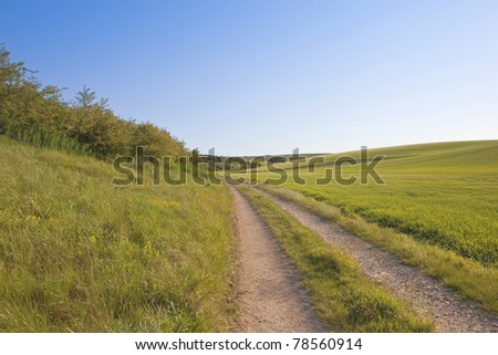 an agricultural landscape with rolling hills and a dusty farm track under a blue sky