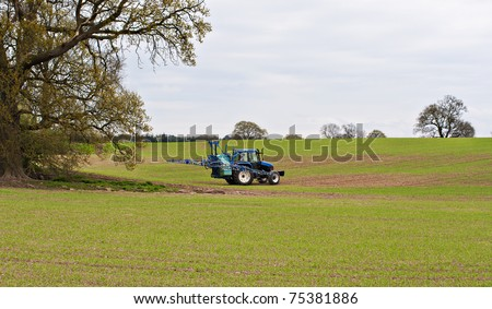 an agricultural tractor about to start it's next run of fertilizing or chemical treatment to a field of new growth crops. - stock photo