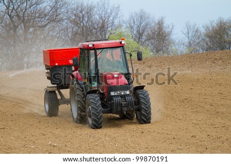 an agricultural tractor starts a chemical treatment run across new growing crops, with copy space below. - stock photo