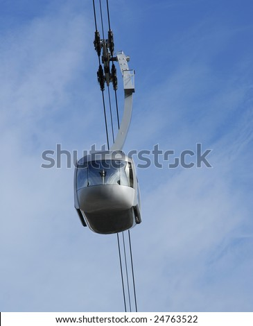 An Air Tram, Cable Car, travels through the blue sky. - stock photo