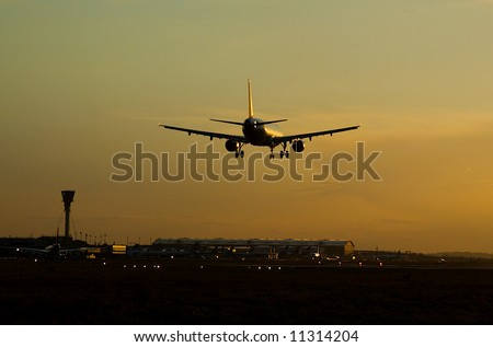 An airliner comes in to touchdown in the late evening - stock photo