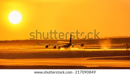 An airliner comes in to touchdown in the sunset - stock photo