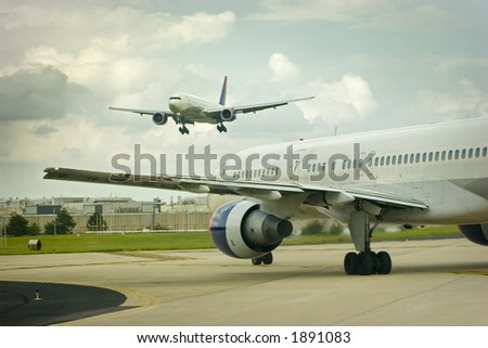 An airplane approaches to land while another awaits departure - stock photo