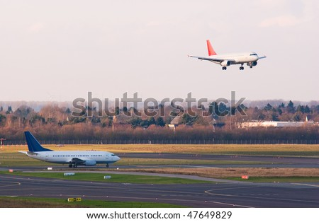An airplane approaches to land while another one prepare for taking off - stock photo