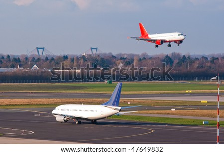 An airplane approaches to land while another one prepare for taking off in Dusseldorf airport - stock photo