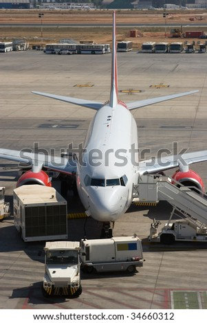 An Airplane at the Gate being Serviced - stock photo