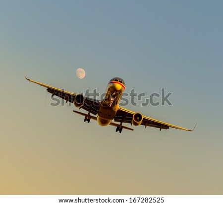 An airplane descends for landing on a moonlit evening just before sunset. - stock photo