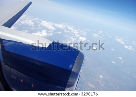 An airplane engine, wing, and the sky