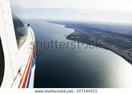 An airplane flying above a body of water. - stock photo