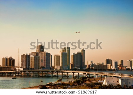 An airplane flying over the skyline of Miami Florida - stock photo