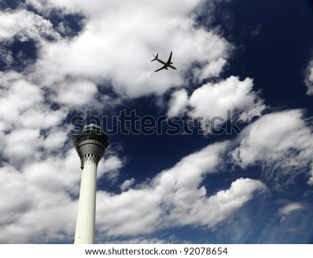 An airplane flying overhead across an airport control tower against a blue cloudy sky. - stock photo