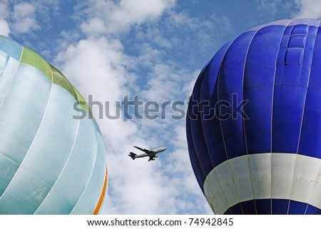 An airplane flying through a blue cloudy sky captured in between two colorful hot air balloon. - stock photo