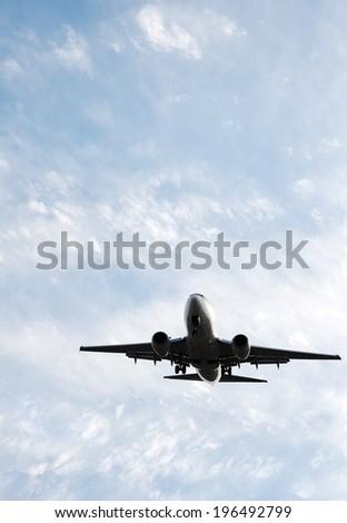 An airplane flying through a partly cloudy sky. - stock photo
