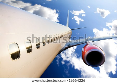An airplane in flight over a blue sky - stock photo