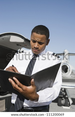 An airplane pilot taking notes on notepad with airplane in the background at airfield - stock photo