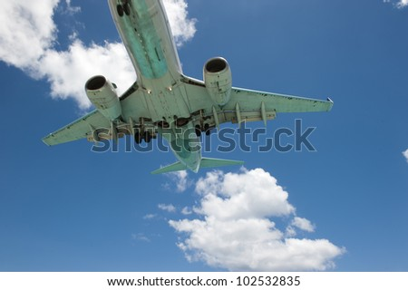 An airplane propelling past camera frame, making it able to capture a bottom shot of the vehicle in motion. - stock photo
