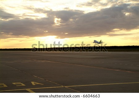 an airplane takes off the airport at sunrise - stock photo