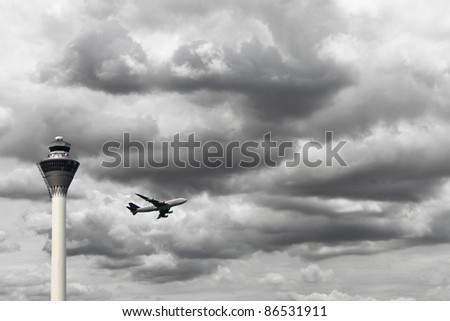 An airplane taking off during a stormy cloudy day overlooking the airport control tower. - stock photo