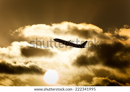 An airplane taking off in beautiful sunset/Flying into Dusk/Sun and Plane - stock photo