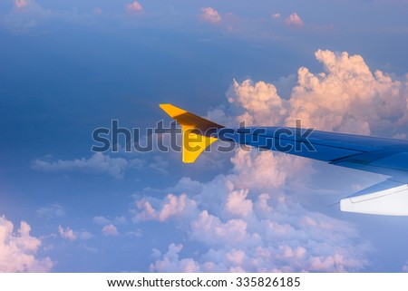 An airplane wing against the sky and clouds up in the air