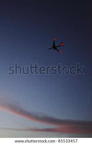 An airplane with blinking tail-light flying high over a surreal evening sky. - stock photo
