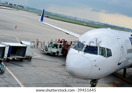An airplane, with the gangway attached getting ready for boarding - stock photo