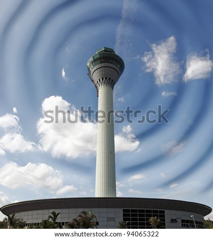 An airport control tower against a blue cloudy sky vibrating visible radar waves. - stock photo