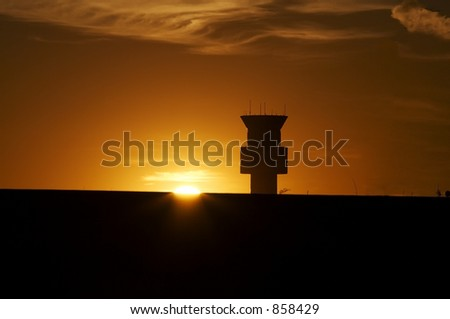 An airport control tower at sunset.