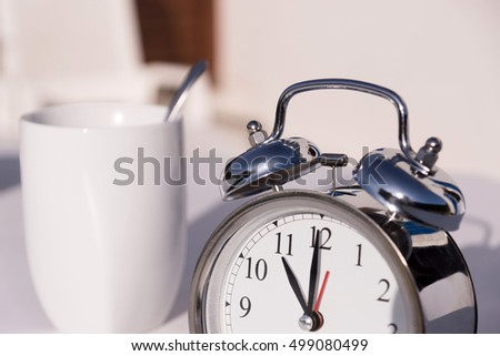 An alarm clock and a coffee cup on a garden table
