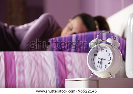 An alarm clock with a sleeping young woman in the background - stock photo