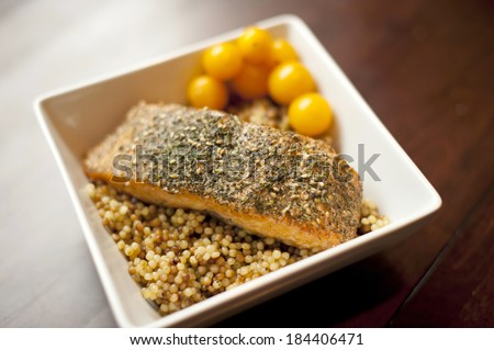 An Alaskan wild salmon grilled and seasoned on a cedar plank placed on top of a couscous with tomatoes on a wooden table. - stock photo
